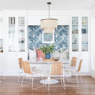 Inspiration pour une salle à manger ouverte sur la cuisine marine de taille moyenne avec un mur blanc, un sol marron et un sol en vinyl.