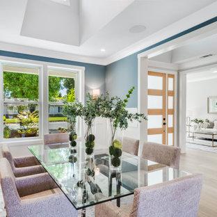 Cette photo montre une grand salle à manger nature fermée avec un mur bleu, un sol en bois clair, aucune cheminée, un sol gris, un plafond voûté et du lambris.