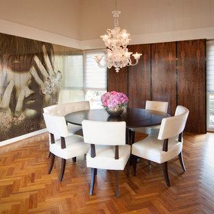 Foto di una sala da pranzo moderna con pavimento in legno massello medio, nessun camino e pareti con effetto metallico