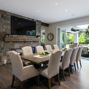 Неиссякаемый источник вдохновения для домашнего уюта: кухня-столовая среднего размера в стиле современная классика с фасадом камина из камня, серыми стенами, темным паркетным полом, коричневым полом и двусторонним камином