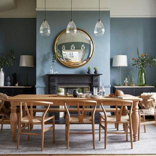 Klassisk inredning av en matplats, med blå väggar, ljust trägolv och en standard öppen spis