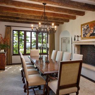 Immagine di una sala da pranzo mediterranea chiusa con pareti bianche, parquet scuro e camino classico