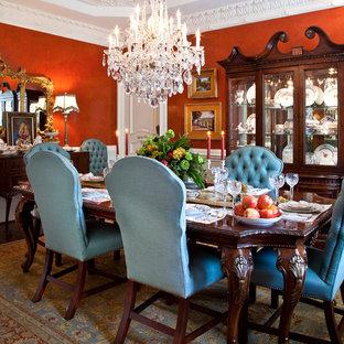 Cette image montre une salle à manger traditionnelle fermée et de taille moyenne avec un sol en bois foncé et un mur orange.
