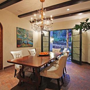 Immagine di una sala da pranzo aperta verso il soggiorno mediterranea di medie dimensioni con pareti beige e pavimento in mattoni