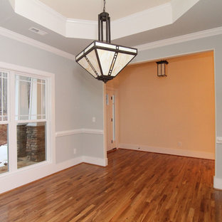 Example of a mid-sized transitional medium tone wood floor enclosed dining room design in Raleigh with blue walls