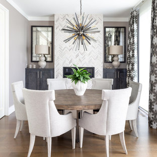 Стильный дизайн: столовая в стиле современная классика с серыми стенами, паркетным полом среднего тона, стандартным камином, фасадом камина из плитки и коричневым полом - последний тренд