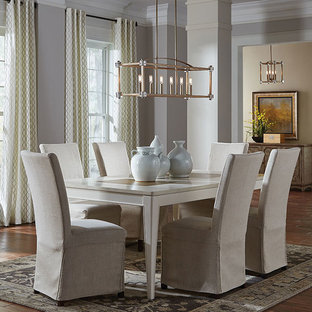 Example of a mid-sized trendy medium tone wood floor and brown floor enclosed dining room design in Other with gray walls and no fireplace