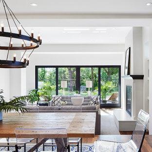 Неиссякаемый источник вдохновения для домашнего уюта: большая гостиная-столовая в средиземноморском стиле с белыми стенами, темным паркетным полом, стандартным камином, фасадом камина из штукатурки и коричневым полом