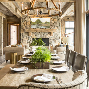 Example of a large mountain style dark wood floor and brown floor great room design in Minneapolis with brown walls, a standard fireplace and a stone fireplace