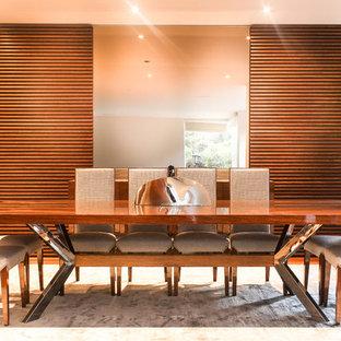 Foto di una grande sala da pranzo aperta verso il soggiorno moderna con pareti marroni, pavimento in compensato e pavimento marrone