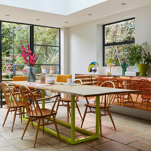 Large contemporary open plan dining room in London with white walls and concrete flooring.