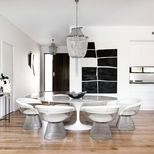 This is an example of a mid-sized contemporary open plan dining in Melbourne with white walls, medium hardwood floors, no fireplace and brown floor.