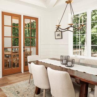 Immagine di una grande sala da pranzo classica con pavimento in legno massello medio, pareti gialle e pavimento marrone