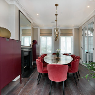 Large contemporary enclosed dining room in London with beige walls, a standard fireplace, medium hardwood flooring, a metal fireplace surround and brown floors.
