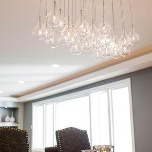 Ispirazione per una sala da pranzo aperta verso la cucina design di medie dimensioni con pareti grigie, parquet chiaro, camino classico e cornice del camino in pietra