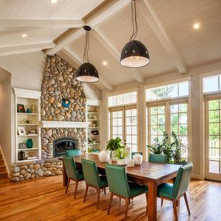 Foto di una sala da pranzo aperta verso il soggiorno tradizionale di medie dimensioni con pareti bianche, cornice del camino in pietra, pavimento in legno massello medio e stufa a legna