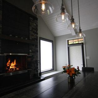 他の地域の広いトランジショナルスタイルのおしゃれなダイニングキッチン (濃色無垢フローリング、標準型暖炉、積石の暖炉まわり、三角天井) の写真