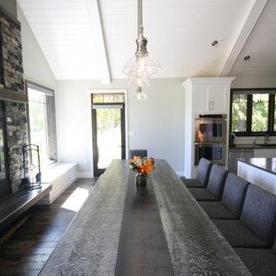 Ispirazione per una grande sala da pranzo aperta verso la cucina classica con parquet scuro, camino classico, cornice del camino in pietra ricostruita e soffitto a volta