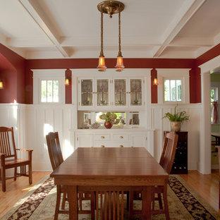 Aménagement d'une grand salle à manger craftsman fermée avec un mur rouge, un sol en bois clair et aucune cheminée.