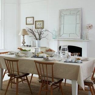 Bild på en stor nordisk matplats, med vita väggar, ljust trägolv, en standard öppen spis och en spiselkrans i gips