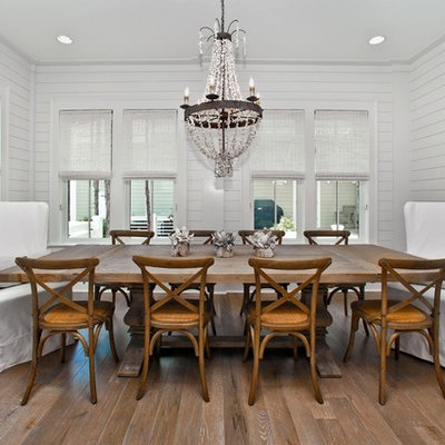 Example of a beach style medium tone wood floor dining room design in Miami with white walls