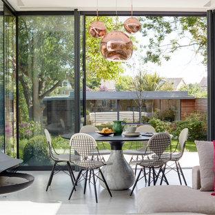 Foto di una sala da pranzo aperta verso il soggiorno minimal di medie dimensioni con pareti bianche, pavimento in cemento, pavimento grigio e camino sospeso