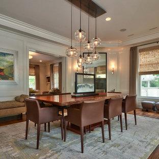На фото: большая отдельная столовая в стиле неоклассика (современная классика) с паркетным полом среднего тона, стандартным камином, фасадом камина из металла и белыми стенами с