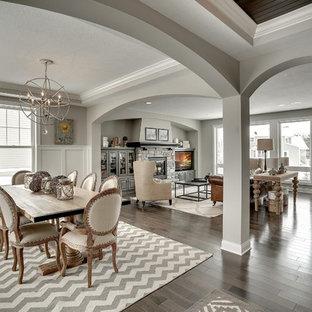 Immagine di una grande sala da pranzo aperta verso il soggiorno tradizionale con pareti grigie, camino classico e cornice del camino in pietra