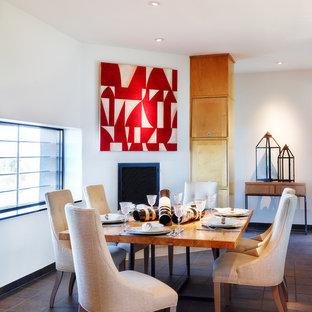 Réalisation d'une salle à manger design avec un mur blanc et une cheminée standard.