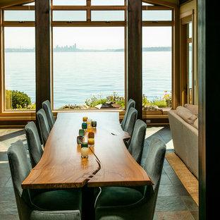 Immagine di una grande sala da pranzo aperta verso il soggiorno stile marino con pareti beige, pavimento in ardesia e pavimento grigio