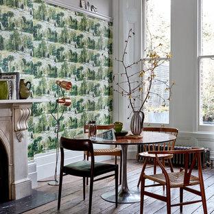 Ejemplo de comedor escandinavo con paredes verdes, suelo de madera oscura, chimenea tradicional y marco de chimenea de piedra