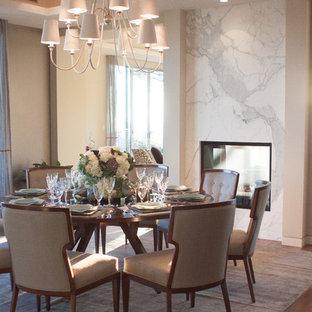 Immagine di una grande sala da pranzo contemporanea chiusa con pareti beige, camino bifacciale, cornice del camino in pietra e parquet scuro