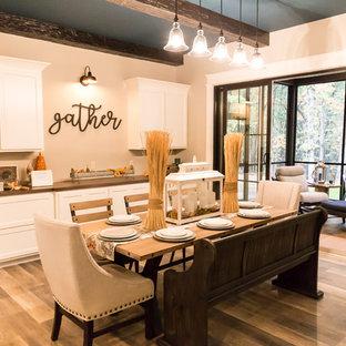 Ispirazione per una sala da pranzo aperta verso il soggiorno chic di medie dimensioni con pareti beige, pavimento in vinile e pavimento marrone