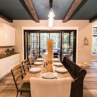 Ejemplo de comedor tradicional renovado, de tamaño medio, abierto, con paredes beige, suelo vinílico y suelo marrón