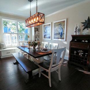 Immagine di una sala da pranzo aperta verso il soggiorno stile americano di medie dimensioni con pareti beige, parquet scuro, camino classico e cornice del camino in mattoni