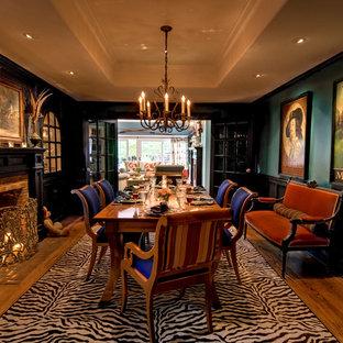 Immagine di una sala da pranzo tradizionale chiusa e di medie dimensioni con parquet scuro, camino classico, cornice del camino in mattoni e pareti verdi