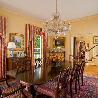Design ideas for a classic enclosed dining room in Dallas with yellow walls and medium hardwood flooring.