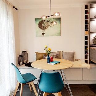 На фото: маленькая кухня-столовая в современном стиле с серыми стенами, темным паркетным полом и черным полом с