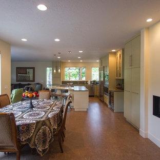 Immagine di una sala da pranzo aperta verso il soggiorno design di medie dimensioni con pareti bianche, pavimento in sughero, camino lineare Ribbon e cornice del camino in intonaco