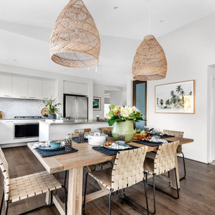 Photo of a beach style kitchen/dining combo in Other with white walls, medium hardwood floors and brown floor.