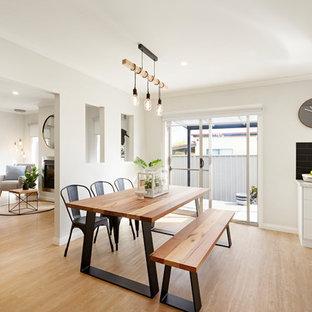 Scandinavian kitchen/dining combo in Other with beige walls, medium hardwood floors and brown floor.
