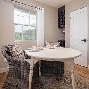 Immagine di una grande sala da pranzo aperta verso la cucina country con pareti beige, pavimento in legno massello medio e pavimento blu