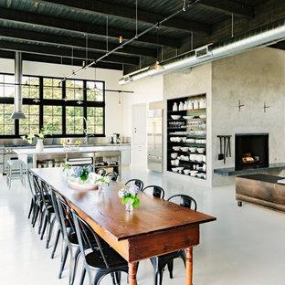Ispirazione per una sala da pranzo aperta verso il soggiorno industriale con pareti beige e pavimento bianco