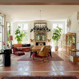 Foto di una grande sala da pranzo aperta verso il soggiorno boho chic con pareti bianche, pavimento in terracotta, camino classico, cornice del camino in intonaco e pavimento arancione