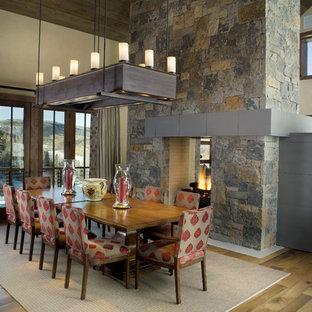 Foto de comedor de cocina rústico, grande, con paredes beige, suelo de madera en tonos medios, chimenea de doble cara y marco de chimenea de piedra