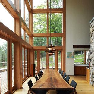 Modelo de comedor rústico, grande, abierto, con paredes blancas, suelo de madera en tonos medios y suelo marrón