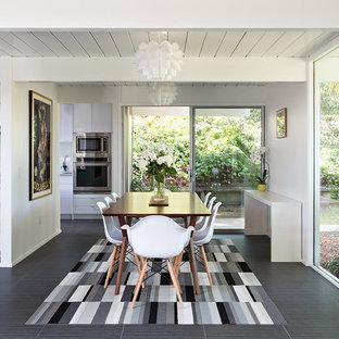 Idee per una sala da pranzo aperta verso la cucina minimalista con pareti bianche e pavimento con piastrelle in ceramica