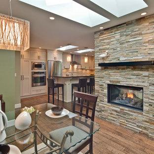 Ejemplo de comedor actual, de tamaño medio, abierto, con paredes verdes, suelo de madera en tonos medios, chimenea de doble cara y marco de chimenea de piedra