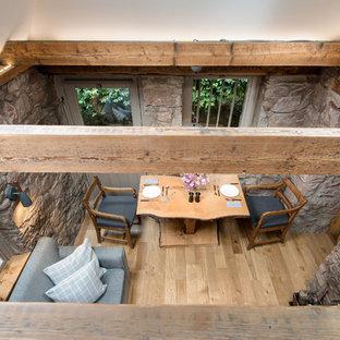 Ejemplo de comedor bohemio, pequeño, cerrado, con suelo de madera en tonos medios y marco de chimenea de piedra