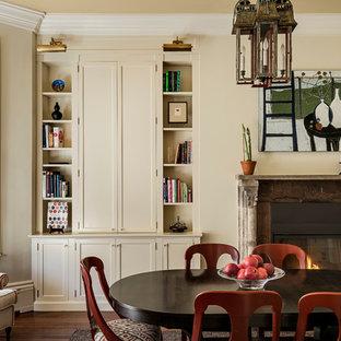 Ejemplo de comedor clásico con paredes beige, suelo de madera oscura, chimenea tradicional y marco de chimenea de madera